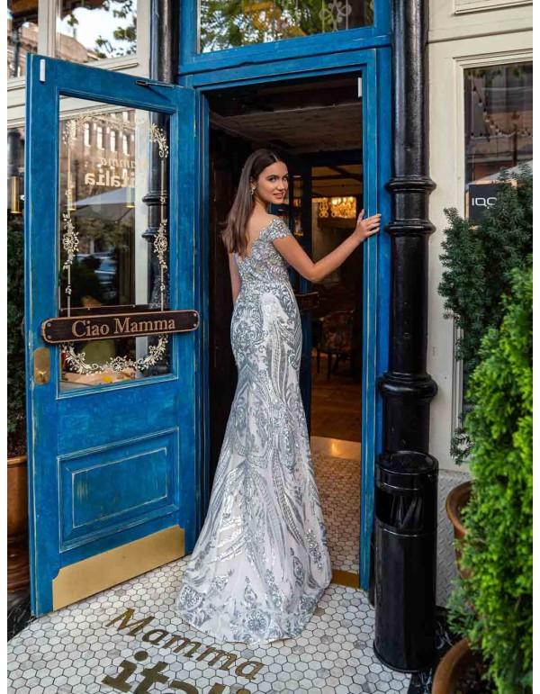Long princess cut party dress with silver brocade and bandeau neckline. en INVITADISIMA