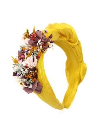 Diadema arrugada en tela sinamay color mostaza adornada con flores y hojas naturales preservadas