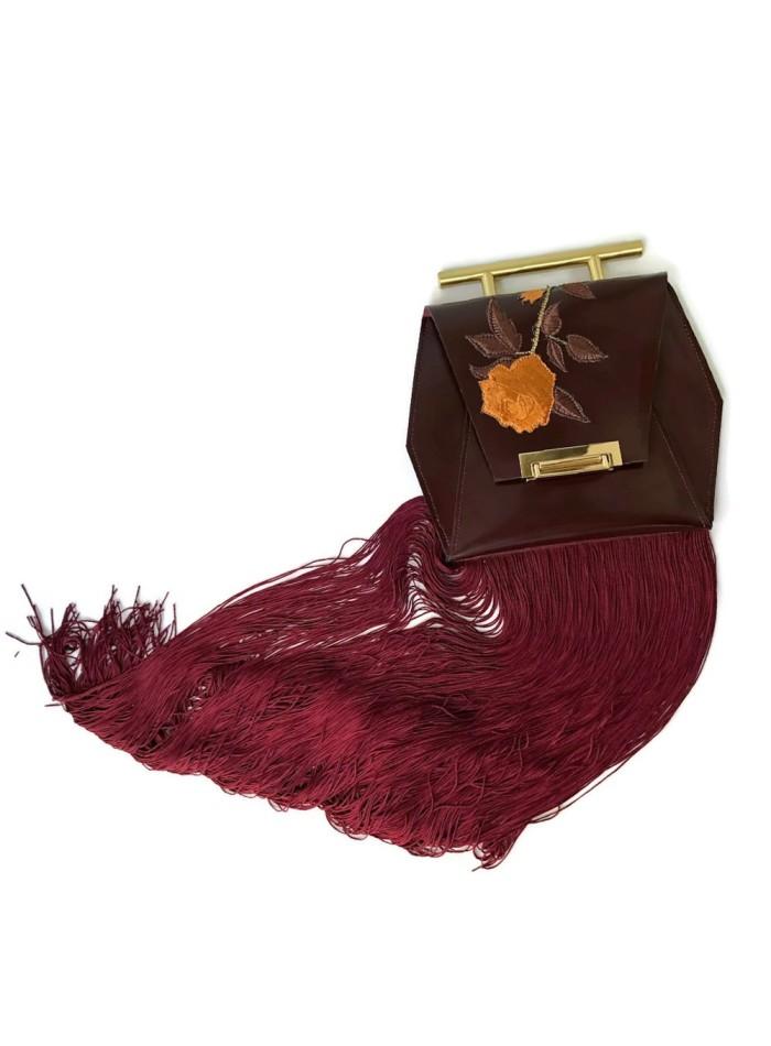 Bolso de piel color vino con detalles de flores bordadas y flecos de Angela Valentine.
